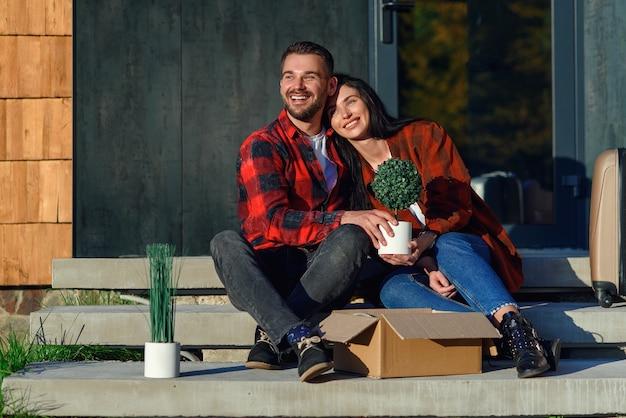Jovem casal sentado na escada se divertindo desfazendo as caixas depois de se mudar para a nova casa.