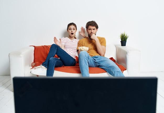 Jovem casal sentado na pipoca do sofá assistindo a um filme relaxante. foto de alta qualidade