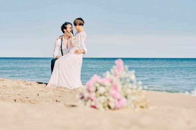 Jovem casal sentado na praia vestido de noiva e noivo com um buquê de flores na areia