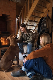 Jovem casal sentado na sala perto da lareira com o cachorro e se aquecendo
