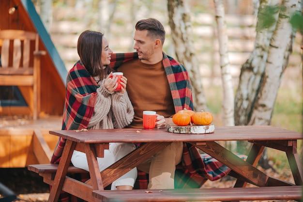Jovem casal sentado na velha mesa de madeira na floresta de outono de sua casa
