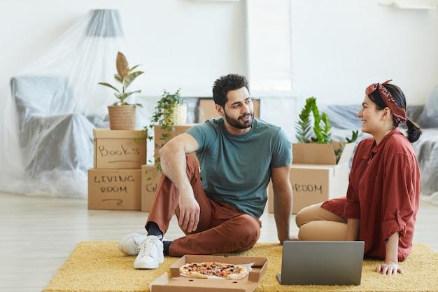 Jovem casal sentado no chão com um laptop, conversando e comendo pizza em sua nova casa