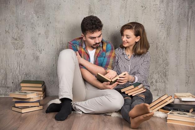 Jovem casal sentado no chão lendo um livro