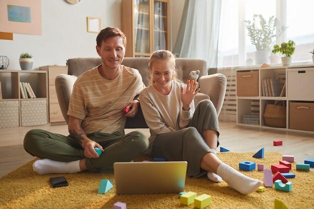 Jovem casal sentado no chão, sorrindo e acenando, olhando para o monitor do laptop, conversando online em casa