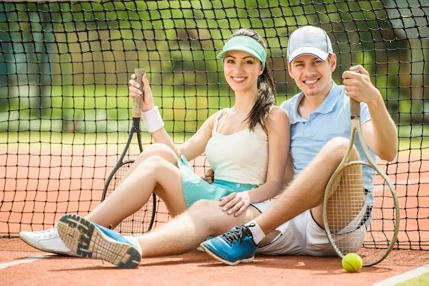 Jovem casal sentado no court de ténis, segurando a raquete de tênis.