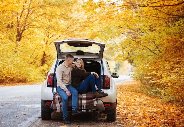 Jovem casal sentado no porta-malas de um carro na estrada no outono