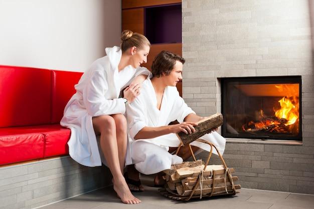 Jovem casal sentado no roupão de banho para lareira
