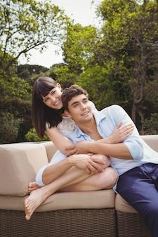 Jovem casal sentado no sofá e abraçando ao ar livre