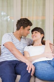 Jovem casal sentado no sofá e olhando um ao outro