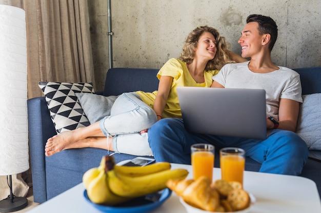 Jovem casal sentado no sofá em casa olhando no laptop