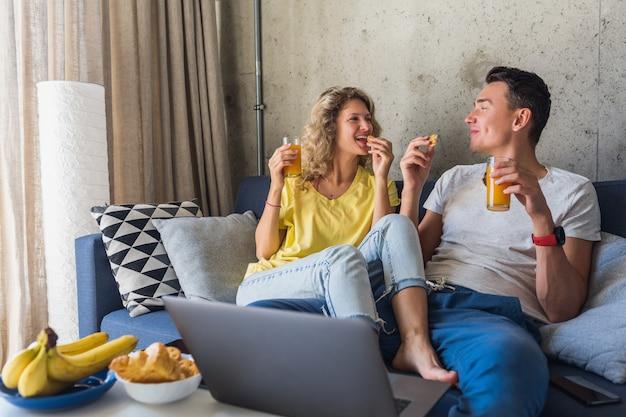 Jovem casal sentado no sofá em casa tomando café da manhã