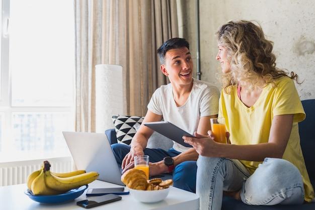 Jovem casal sentado no sofá em casa trabalhando online em um laptop e tablet