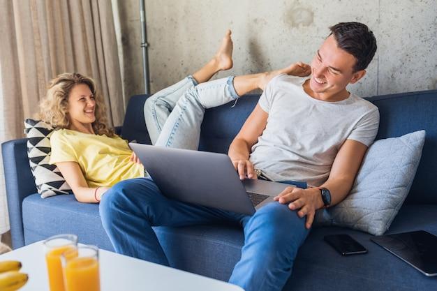 Jovem casal sentado no sofá em casa usando laptop, brincando e flertando