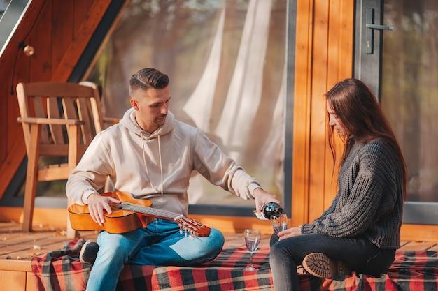 Jovem casal sentado no terraço de sua casa no outono
