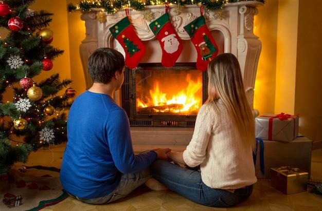 Jovem casal sentado sob uma árvore de natal olhando para a lareira acesa