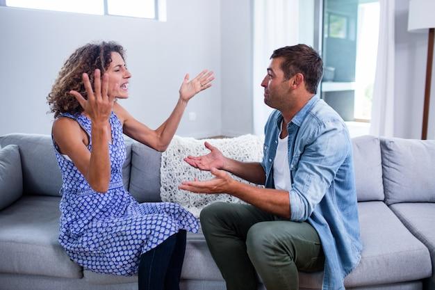 Jovem casal sentados juntos e discutindo depois de uma briga