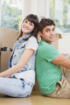 Jovem casal sentados juntos no chão e sorrindo em sua nova casa