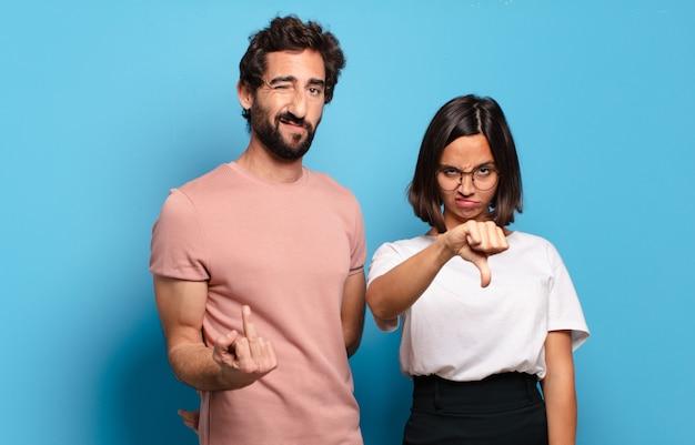 Jovem casal sentindo-se zangado, irritado, irritado, desapontado ou descontente