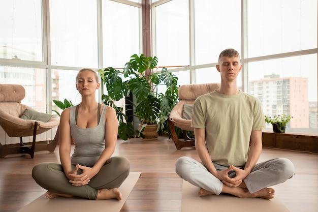 Jovem casal sereno em roupas esportivas cruzando as pernas enquanto está sentado em colchonetes e praticando exercícios de meditação juntos em casa