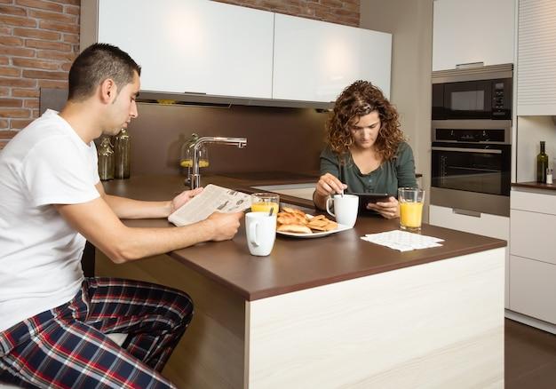 Jovem casal sério lendo notícias em um tablet digital e jornal enquanto toma o café da manhã na cozinha de casa