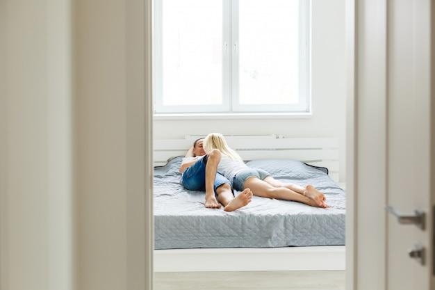 Jovem casal sexy apaixonado, deitada na cama no hotel, abraçando em lençóis brancos, close-up pernas, clima romântico
