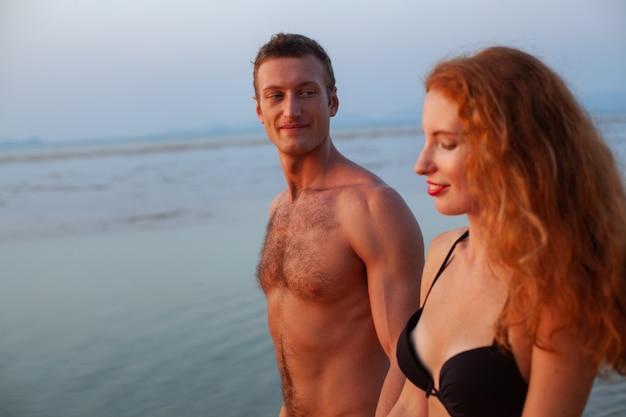 Jovem casal sexy e romântico apaixonado feliz na praia de verão juntos se divertindo usando maiôs