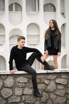 Jovem casal sexy em roupas pretas, posando com um fundo na parede branca
