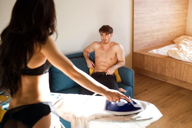 Jovem casal sexy na sala de estar. vista traseira da mulher no carrinho de lingerie preta e camisa branca de ferro. cara se senta no sofá na frente da modelo. momento sedutor e sensual.