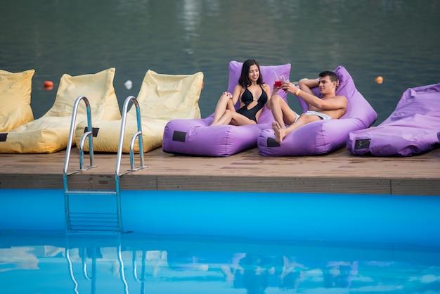 Jovem casal sexy relaxante com bebidas nas espreguiçadeiras almofadadas pela piscina e rio no fundo