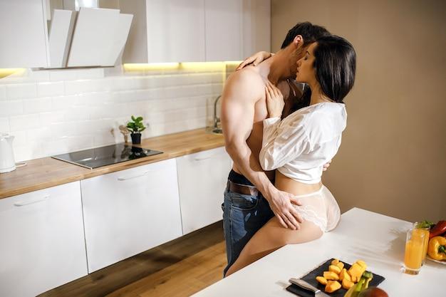 Jovem casal sexy tem intimidade na cozinha à noite. um cara bem construído sem camisa se inclina para a mulher e a beija. modelo sensual quente tocar homem e sentar-se na mesa. use camisa branca e lingerie.