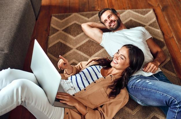 Jovem casal sonhando deita-se no chão, no tapete em casa. um casal está relaxando na sala de estar. uma mulher com um laptop deita-se sobre um homem no chão. trabalho a partir de casa. compras online.
