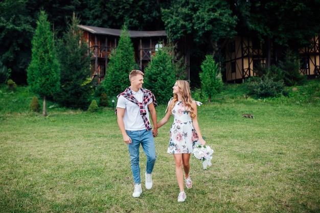 Jovem casal sorridente andando no campo com flores no parque de verão.