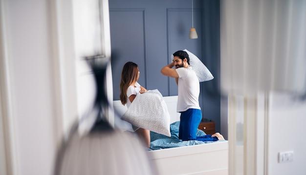 Jovem casal sorridente bonito brigando com almofadas no quarto.