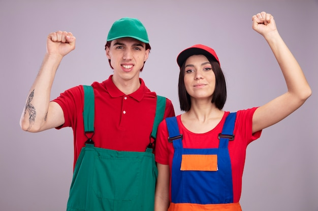 Jovem casal sorridente cara feliz garota com uniforme de trabalhador da construção civil e boné olhando para a câmera fazendo gesto de bater isolado na parede branca