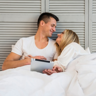 Jovem casal sorridente com tablet debaixo do cobertor na cama