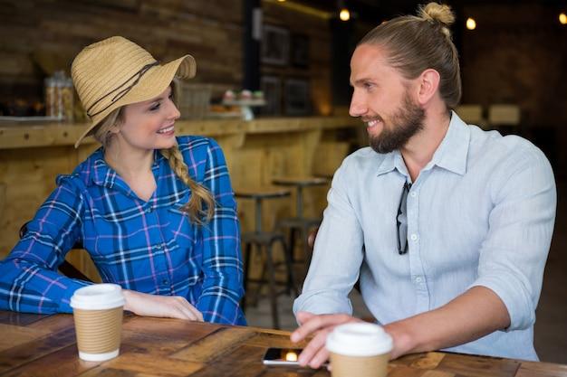 Jovem casal sorridente conversando à mesa de um café