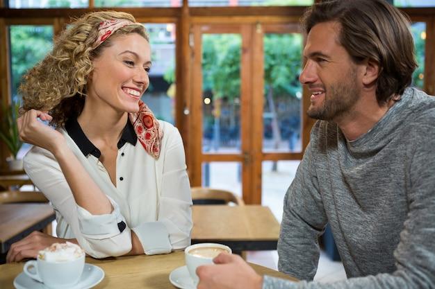 Jovem casal sorridente conversando à mesa do refeitório