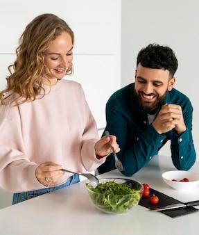 Jovem casal sorridente cozinhando em casa juntos
