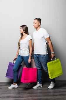 Jovem casal sorridente de estudantes ensolarados segurando várias sacolas de compras coloridas isoladas no fundo branco