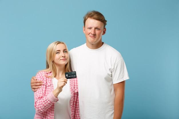 Jovem casal sorridente, dois amigos, cara e mulher em camisetas brancas vazias em branco rosa posando