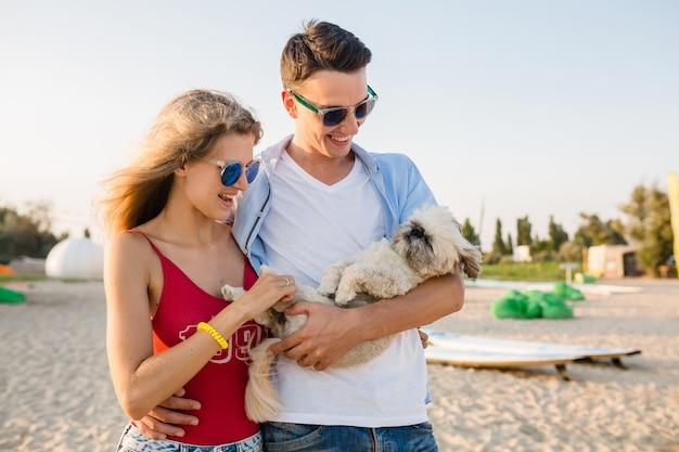 Jovem casal sorridente e atraente se divertindo na praia brincando com o cachorro da raça shih-tsu