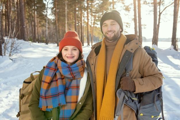 Jovem casal sorridente em um agasalho de inverno quente em pé na frente da câmera contra a neve e a floresta mista e olhando para você em um dia ensolarado