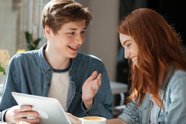 Jovem casal sorridente falando enquanto estiver usando tablet