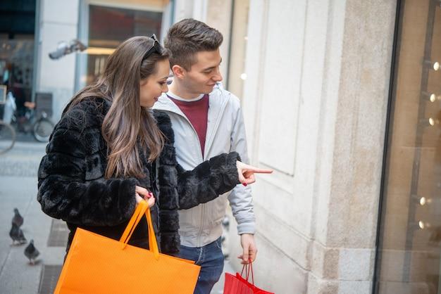 Jovem casal sorridente fazendo compras em uma rua urbana