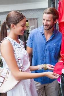 Jovem casal sorridente feliz olhando roupas