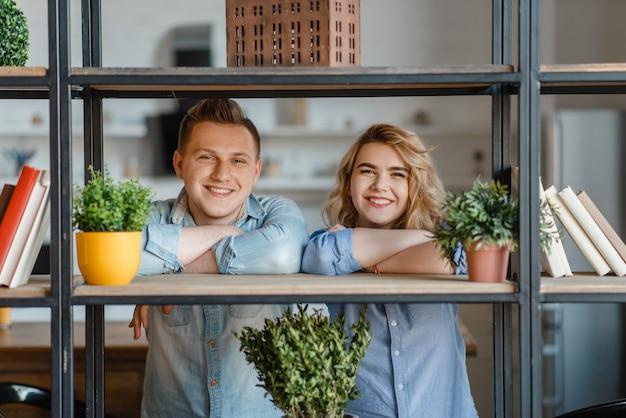 Jovem casal sorridente na prateleira com plantas caseiras, passatempo de florista.