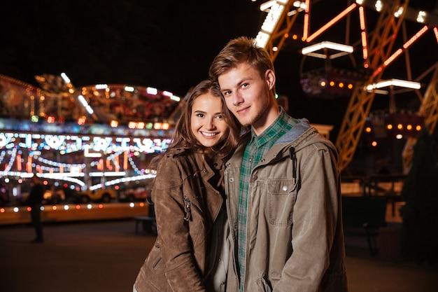 Jovem casal sorridente no parque de diversões.