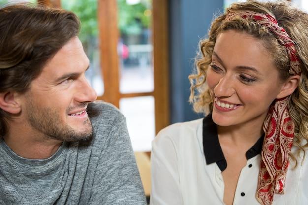 Jovem casal sorridente, olhando um para o outro em uma cafeteria