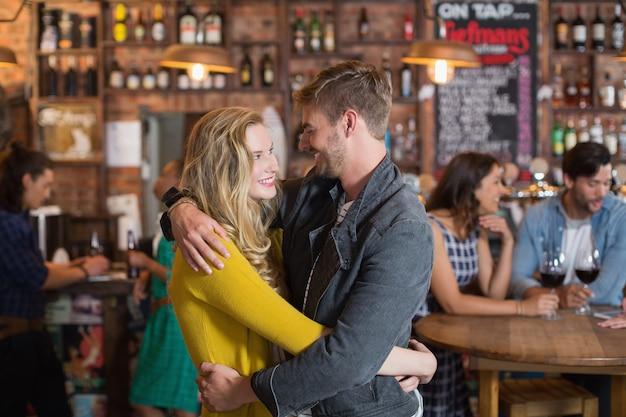 Jovem casal sorridente, olhando um para o outro enquanto se abraçam