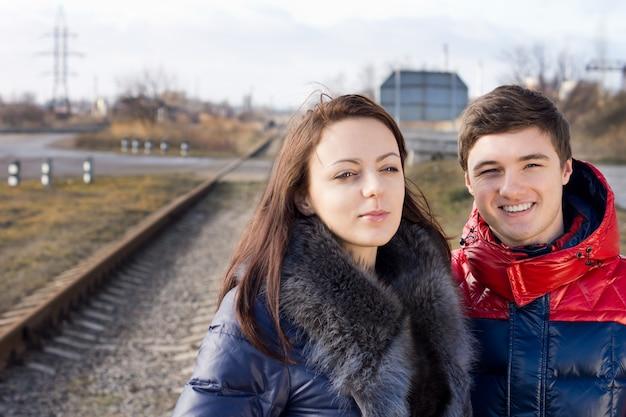 Jovem casal sorridente, parado juntos, esperando ao lado de uma linha ferroviária rural com uma passagem de nível atrás deles enquanto esperam o trem